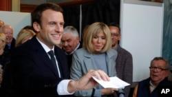 Kandidat presiden dari sayap tengah, Emmanuel Macron, kiri, bersiap untuk memberikan suaranya, bersama dengan sang istri, Brigitte, dalam putara pertama pilpres Perancis di Le Touquet, Perancis bagian utara, 23 April 2017. (foto: Philippe Wojazer, Pool photo via AP)