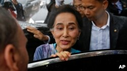 FILE - Myanmar State Counselor Aung San Suu Kyi leaves a meeting with migrant workers at the coastal fishery center of Samut Sakhon, Thailand, June 23, 2016.