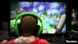 FILE - A child plays video game Minecraft in London, July 4, 2015.