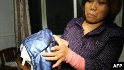 حملات مرگبار با کارد در چین بیسابقه نیست. در این جا مادری جراحات پسرش را در حادثه ای مشابه نشان می دهد. (گوانگشو: دسامبر ۲۰۱۲ )