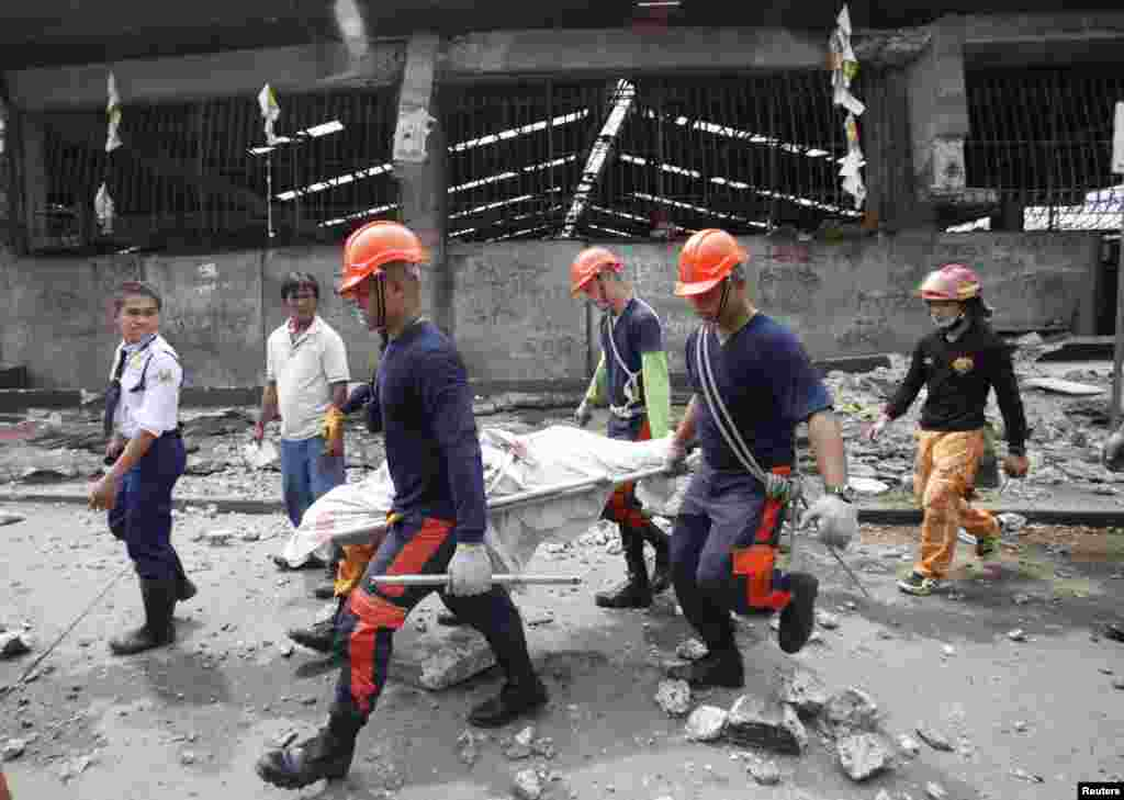 Rescue members recover the body of a vendor killed after an earthquake hit Pasil market in Cebu, central Philippines, Oct. 15, 2013.