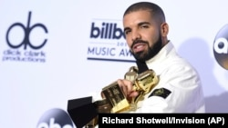 Drake poses in the press room with his 13 awards at the Billboard Music Awards.