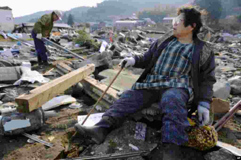 A woman looks out over the destroyed landscape in Ofunato City, Iwate Prefecture in northern Japan, after an earthquake and tsunami struck the area, March 13, 2011.