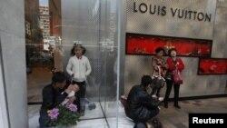 Du khách Trung Quốc ngồi trước của tiệm LV tại Hồng Kông. Cư dân ở Hồng Kông cũng phải chật vật ứng phó với làn sóng du khách đến từ Hoa Lục.