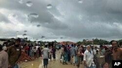 Rohingya refugees walk under rain clouds on June 26, 2018, in Jamtoli refugee camp in Bangladesh.