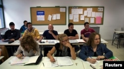 FILE - Victor Antu–a of Spain (top R) and Felipe Barbosa of Colombia (top 2nd R) attend an English class at an Adults Education Centre in Madrid.