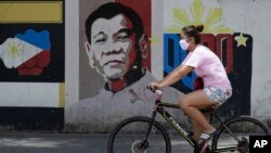 A woman wearing a protective mask rides her bicycle past an image of Philippine President Rodrigo Duterte in Manila, Philippines on Friday March 20, 2020. The Philippines is indefinitely banning the entry of foreigners after the government declared…