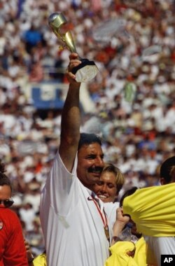 FILE - U.S. women's soccer team head coach Tony DiCicco celebrates by holding the trophy aloft after defeating China in the Women's World Cup Final at the Rose Bowl in Pasadena, Calif., July 10, 1999.