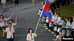 FILE - Cambodian flag-bearer Davin Sorn leads her nation's contingent in the athletes parade during the opening ceremonies of the London 2012 Olympic Games at Olympic Stadium, July 27, 2012.
