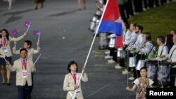 Cambodia's flagbearer Davin Sorn holds the national flag as she leads the contingent in the athletes parade during the opening ceremony of the London 2012 Olympic Games at the Olympic Stadium July 27, 2012.
