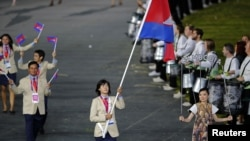 Cambodia's flagbearer Davin Sorn holds the national flag as she leads the contingent in the athletes parade during the opening ceremony of the London 2012 Olympic Games at the Olympic Stadium July 27, 2012. REUTERS/Mike Blake