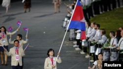 Cambodia's flagbearer Davin Sorn holds the national flag as she leads the contingent in the athletes parade during the opening ceremony of the London 2012 Olympic Games at the Olympic Stadium July 27, 2012. REUTERS/Mike Blake (BRITAIN - Tags: SPORT OLYMPICS)