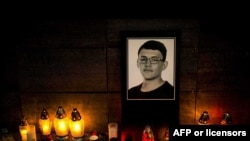 Candles and a portrait of Slovak investigative journalist Jan Kuciak