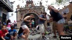 FILE - Tourists react to a flock of pigeons as they visit Parque de las Palomas in San Juan, Puerto Rico, July 18, 2015.