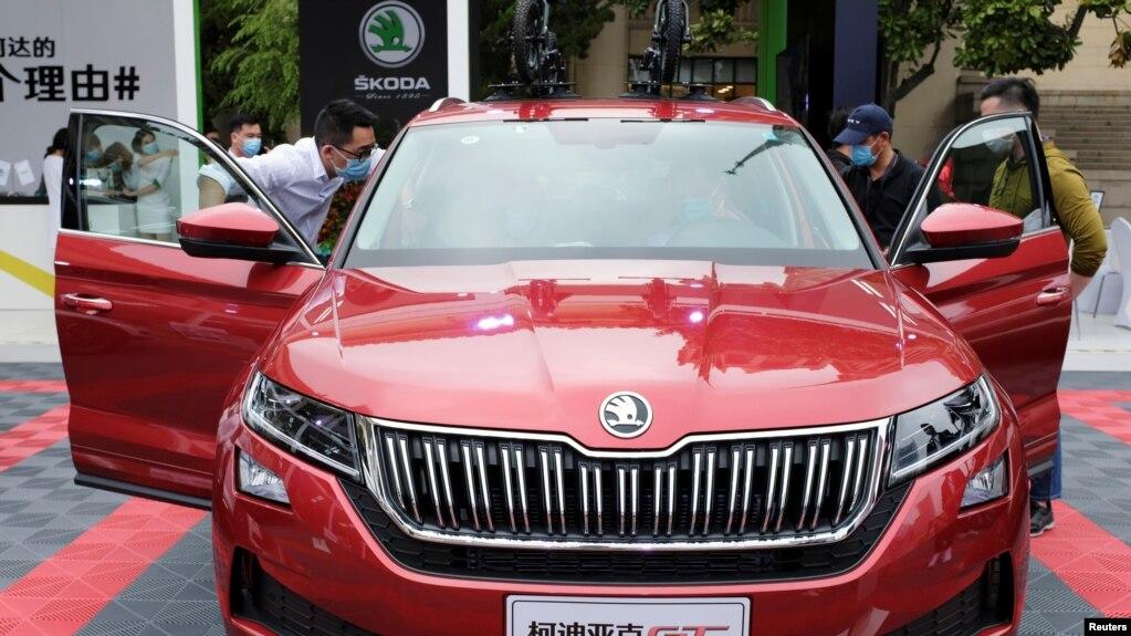戴着口罩的参观者在上海举行的一个汽车销售会上查看斯柯达牌的汽车。(资料照: 2020年5月5日)