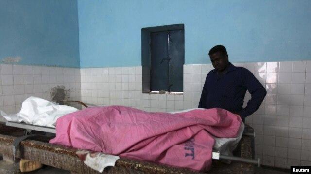 Seorang wartawan memeriksa jenazah rekannya yang tewas akibat kekerasan di Somalia (foto: dok). Kelompok HAM Human Rights Watch menuntut pembebasan wartawan yang ditahan di Mogadishu.