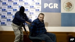 "Jesus Reynaldo Zambada Garcia, known as Jesus ""The King"" Zambada, a leader in the Sinaloa drug cartel, is pushed in a chair by a masked police officer as Garcia is presented to the press in Mexico City, Wednesday, Oct. 22, 2008. (AP Photo/Alexandre Meneg"