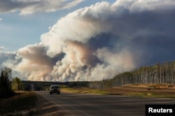 FILE - Smoke billows from the Fort McMurray wildfires as a truck drives down the highway in Kinosis, Alberta, Canada, May 5, 2016.