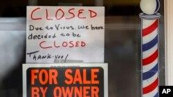 """美国密西根州一家理发店门前打出""""受新冠病毒影响本店关门""""的告示(2020年4月2日)。新冠病毒疫情已经导致美国1000多万人失业。"""