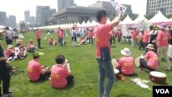 한국 통일부 주최로 지난 27일부터 29일까지 서울에서 열린 통일박람회에서 탈북민들이 고향 이름이 적힌 옷을 입고 춤을 추고 있다.