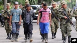 ທະຫານນຳຕົວຜູ້ຕ້ອງສົງໄສຕໍ່ຕ້ານລັດຖະບານ ກຸ່ມກອງທັບປະຕິວັດ ແຫ່ງ ໂຄລົມເບຍ ຫຼື (FARC) ຜູ້ທີ່ໄດ້ຍອມຈຳນົນຕໍ່ພວກທະຫານ ໃນເມືອງ Medellin, ປະເທດ ໂຄລົມເບຍ. 20 ກັນຍາ, 2012.