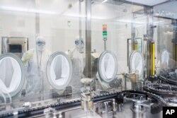 Lab technicians fill vials of investigational coronavirus disease (COVID-19) treatment drug remdesivir at a Gilead Sciences facility in La Verne, California, U.S. March 18, 2020.