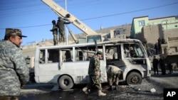 Petugas keamanan Afghanistan menginspeksi minibus yang hancur akibat serangan bom bunuh diri di Kabul, Afghanistan (11/12).