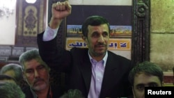 Iran's President Mahmoud Ahmadinejad (C) gestures in front of the shrine of Prophet Muhammad's grandson Hussein ibn Ali at the Al-Hussein mosque, in old Cairo, Egypt, Feb. 5, 2013.