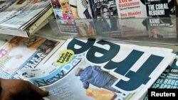 """Seorang pembeli memegang surat kabar """"The New Day"""" di pusat kota London, Inggris, 29 Februari 2016 (Foto: dok)."""