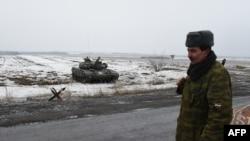 Seorang tentara separatis pro-Rusia berjaga-jaga di Pos Keamanan di Enakieve, 25 km dari kota timur Rusia, Debaltseve (29/1).