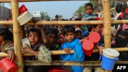 Rohingya refugees wait for food aid at Thankhali refugee camp in Bangladesh's Ukhia district on Jan. 12, 2018.