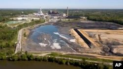 FILE -The Richmond city skyline can be seen on the horizon behind the coal ash ponds along the James River near Dominion Energy's Chesterfield Power Station in Chester, Va., May 1, 2018.