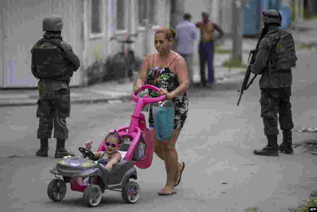 Soldiers of Brazil's Armed Forces, backed by armored vehicles, aircraft and heavy engineering equipment (not shown), take part in an operation in the violence-plagued favela of Vila Kennedy, in Rio de Janeiro.
