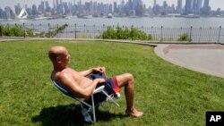 里克·斯圖亞特在新澤西州威霍肯的一家公園曬太陽。遠方是紐約市的天際線。 (2018年5月15日)