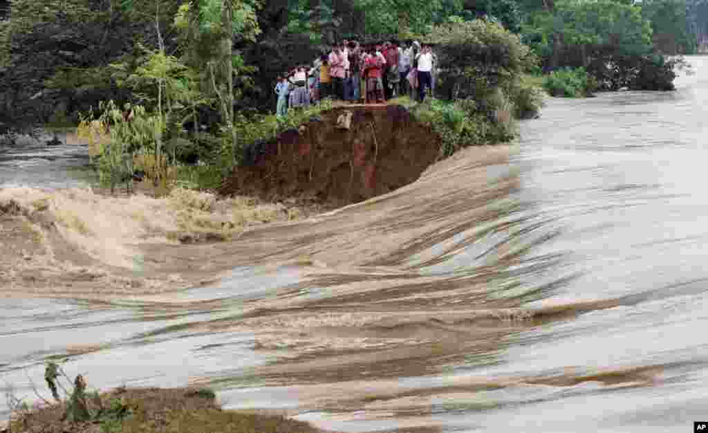 Indian villagers stand on the breached embankment of swollen Kangsabati river at Samat village in West Bengal state. Heavy torrential rain in the aftermath of weakened Cyclone Phailin have made rivers to overflow in the state.