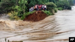 Indian villagers stand on the breached embankment of swollen Kangsabati river at Samat village in West Bengal state, India, Oct. 15, 2013.