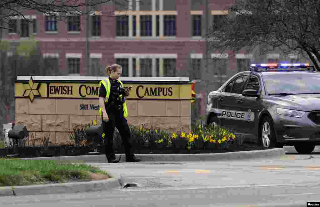 An Overland Park, Kansas police officer guards the entrance to the scene of a shooting at the Jewish Community Center of Greater Kansas City in Overland Park, Kansas, April 13, 2014.