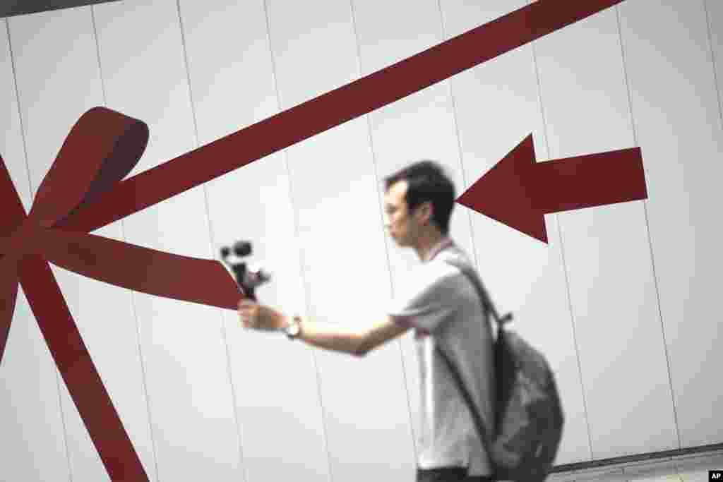 A man takes a selfie at the Ginza shopping district in Tokyo, Japan.