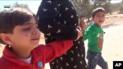叙利亚反对派活动人士新闻网络提供的视频截图显示,一名成年人从空袭现场救出两名儿童。
