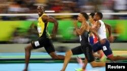 Le Jamaïcain Usain Bolt regarde le Canadien André De Grasse lors des demi-finales 100 mètres homme, à Rio de Janeiro, Brésil, le 14 août 2016.