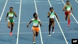 Marie-Josée Ta Lou de la Côte d'Ivoire, à l'extrême gauche, Ruddy Zang Milama du Gabon, deuxième à gauche, Tynia Gaither de Bahamas, deuxième à droite, et Sunayna Wahi de Surinam, à l'extrême droite, disputent une course de 100 mètres-dames aux Jeux Olymp