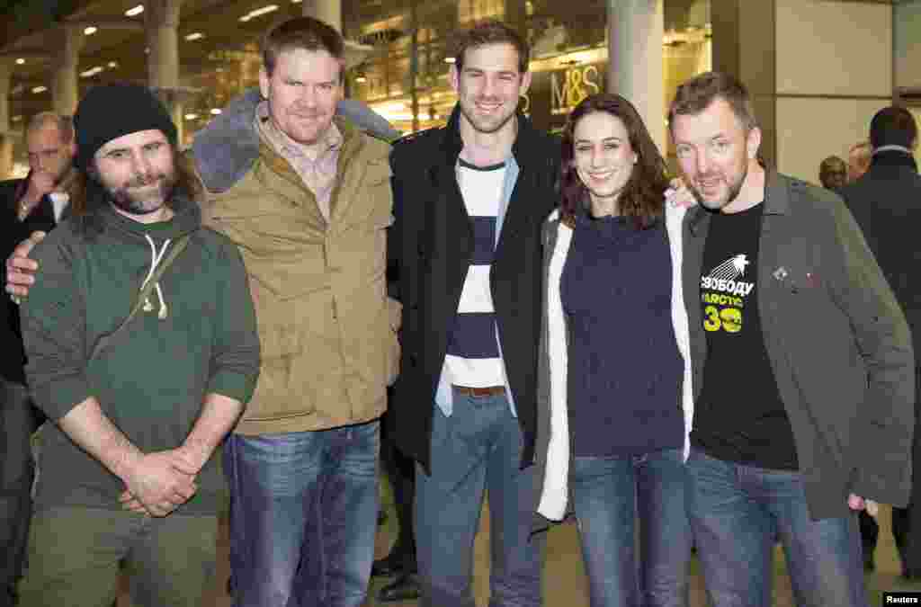 Greenpeace activists Iain Rogers (L), Anthony Perrett (2nd L), Alexandra Harris (2nd R), Phillip Ball (R) and video cameraman Kieron Bryan (C) pose for photographers after arriving at St. Pancras station in central London, England, Dec. 27, 2013.