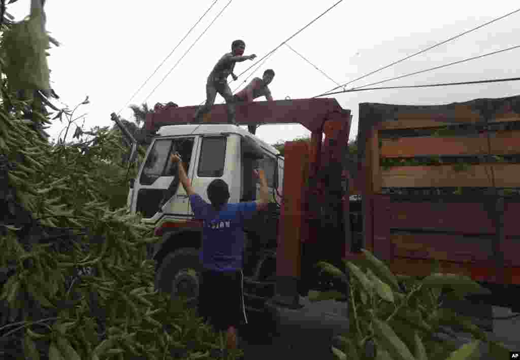 Workers clear a highway of toppled trees after Typhoon Bopha made landfall in Compostela Valley, Philippines, December 4, 2012.