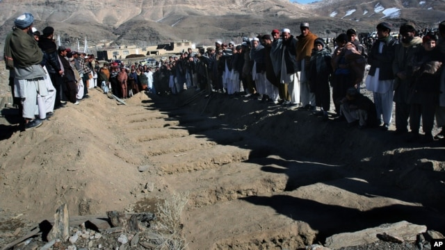 Villagers stand in front of the graves of people killed during an explosion in Sayedabad, Wardak southwest of Kabul, Afghanistan, Jan. 13, 2013.