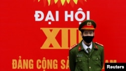 A police officer stands guard in front of a poster for the upcoming 13th national congress of the Communist Party of Vietnam on a street in Hanoi, Vietnam January 20, 2021. REUTERS/Kham