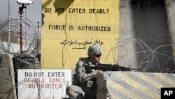 A US soldier controls the area outside the gate of a US base, April 2, 2011 (file photos).