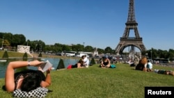 FILE - A woman reads a book as she rests in a public garden near the Eiffel Tower on a hot summer day in Paris, July 3, 2014.