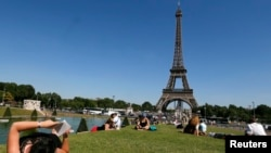 FILE - A woman reads a book as she rests in a public garden near the Eiffel Tower on a hot summer day in Paris, July 3, 2014. REUTERS/Gonzalo Fuentes (FRANCE - Tags: TRAVEL ENVIRONMENT SOCIETY) - RTR3X04W