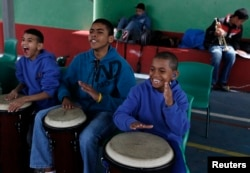 FILE - From left, students Joao Farias Alves, 11, Antonio Marques, 16, and Joao Pedro dos Santos Teixeira, 11, play bongos during their music class at the Madre Lucie Bray Municipal School for the Deaf in Sao Paulo, Sept. 4, 2012. The technique of teaching music to deaf children was developed by Fabio Bonvenuto while working in this public school in 2005, where the percussionists feel the music through vibrations rather than sound waves.