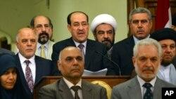 Manm palman irakyen an ap tande Premye Minis Nouri al-Maliki (nan mitan) pandan li tap li yon mesaj kote li anonse demisyon n aprè 8 tan li pase kòm chèf gouvènman an (Bagdad, 14 out 2014).